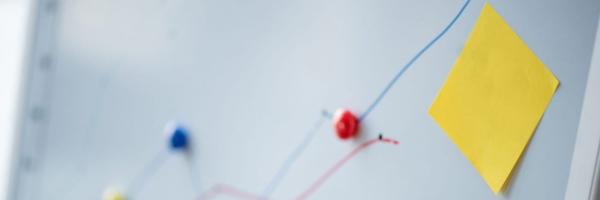 Imagem de um post it amarelo colado na parede com alguns pontos ligando um fio em outro. Essa imagem simboliza o artigo sobre mapeamento de processos do seu laboratório.